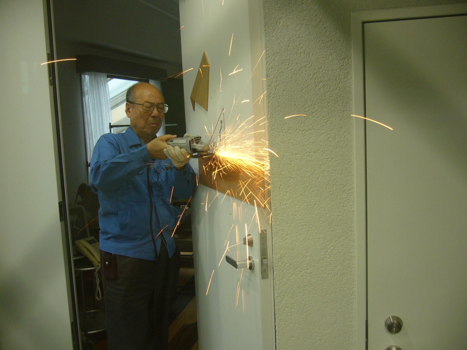 """"""" alt=""""試作室入口のドアを宮本茂紀自ら取り付ける"""""""